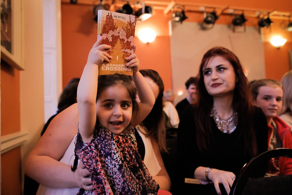 This little girl from Syria is part of a family that spoke to Jane Mitchell in her research for A Dangerous Crossing, and now some of her story is in the book above her head.